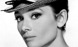 Одри Хепберн – это символ грации, женственности и красоты 50-х годов. До сих пор ее изображение используется во многих модных коллекциях, в глянцевых журналах. Она покорила сердца миллионов людей своей невинной красотой, юностью, изяществом и огромными глазами олененка. Одним из самых запоминающихся образов актрисы является высокая прическа и особенный макияж. С его помощью можно создать замечательный вечерний стиль, который обязательно привлечет внимание! Создание макияжа от Одри Хепберн У Одри тени на глазах никогда не были заметны, поэтому яркие варианты не подойдут. Чтобы подчеркнуть естественный макияж, лучше всего воспользоваться нежно-розовыми или светло-бежевыми оттенками, которые будут практически сливаться с тоном кожи, но придавать выразительность. Внешние уголки можно слегка оттенить матовыми тенями натурального земельного цвета. Внутренний край нижнего века стоит подвести мягким натуральным карандашом светлого цвета. На верхнем веке по линии роста ресниц нужно провести линию темно-коричневым цветом, чтобы она слегка утолщалась в сторону виска. Внизу просто равномерно подвести веко. Все пробелы между ресницами следует закрасить карандашом и в несколько слоев нанести тушь. Глаза не должны выглядеть слишком неестественными, поэтому стоит постараться, чтобы не переборщить. Важно помнить, что для такого макияжа нужна аккуратная форма бровей, без выбивающихся волосков. Они не должны быть слишком тонкими или, наоборот, широкими. Потребуется естественное тональное средство, подобранное под тон кожи. Создание прически от Одри Хепберн Дополнить стиль необходимо прической, которая прекрасно подойдет к абсолютно любому типу лица благодаря своей универсальности. Для начала пряди нужно обработать гелем или воском, собирая их в тугой и высокий хвост. Если планируется делать пышный и объемный пучок, то локоны необходимо еще и начесать. За кончики волос стоит слегка потянуть, чтобы натянуть их до конца. Теперь их необходимо разделить на несколько небольших прядей, кажду